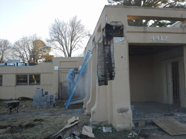 [Image: One of our crew carefully checking the outside of the building during the demolition process.]